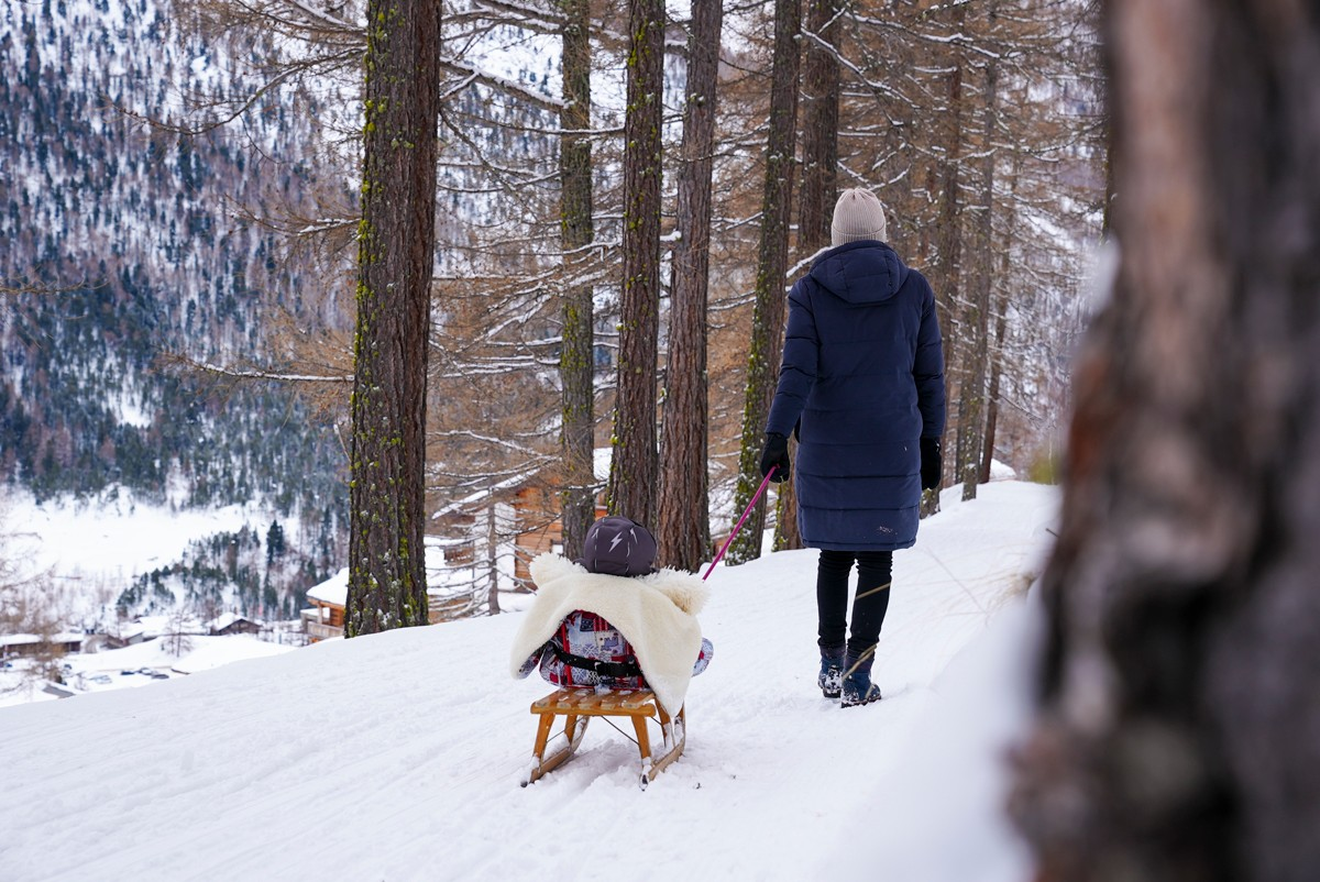 Woman pulling sledge in the forest