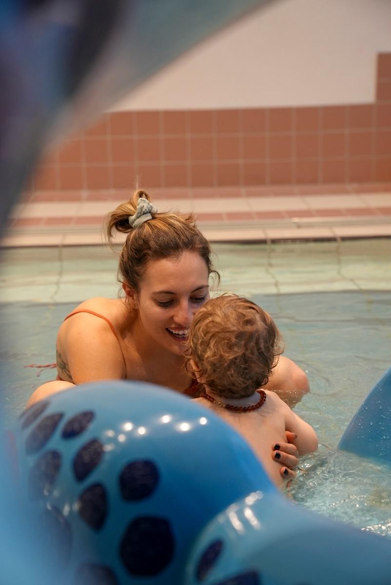 Frau spielt mit Baby im Wasser