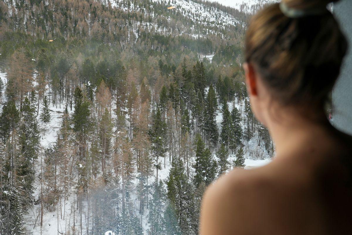 Frau blickt aus Fenster auf Wald