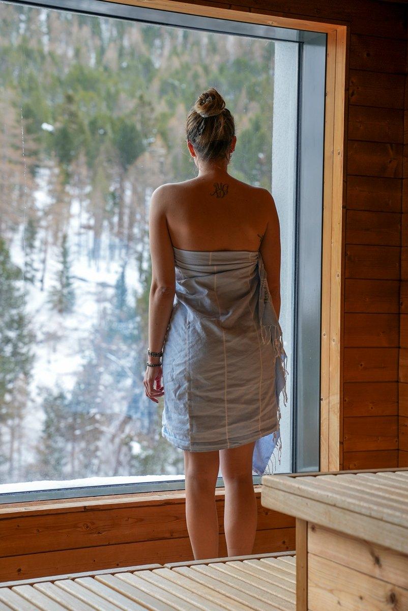 Frau blickt von Sauna aus Fenster