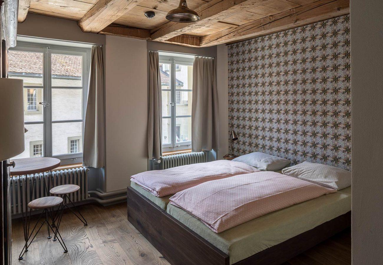 Zimmer mit Doppelbett und Tisch