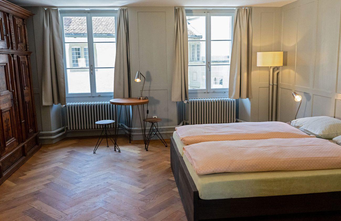 Zimmer mit Doppelbett, antikem Schrank und Tisch