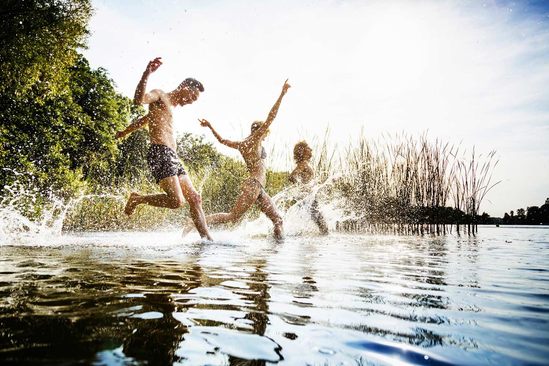 Drei Personen springen ins Wasser