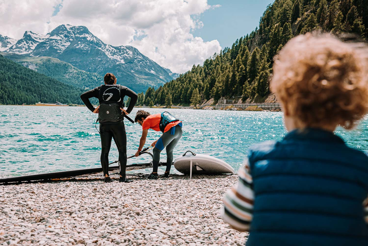 Son observes father and kite instructor on the shore of Lake Silvaplana