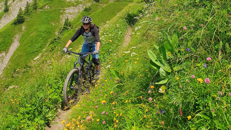 Frau auf dem Bike fährt über den Waldweg